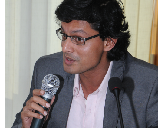 Photo of Shamnad speaking on a microphone at a conference