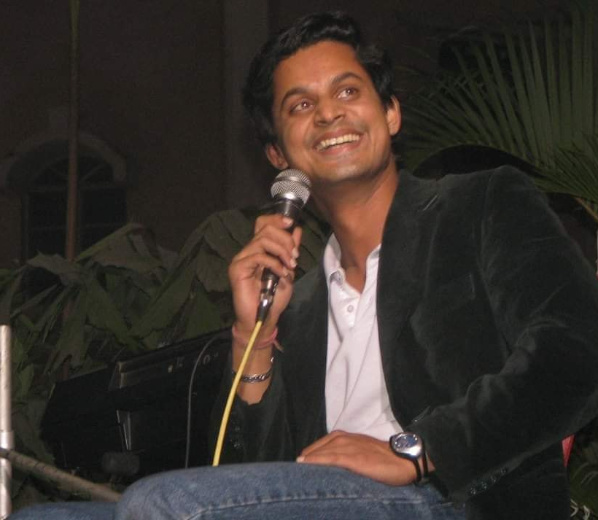 Photo of Shamnad holding a microphone and smiling
